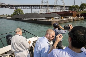 Petroleum coke on Calumet River South Side environmental activists take pictures of a barge carrying petroleum coke waste as they tour Calumet River in Chicago on Monday, Sept. 9, 2013, to see giant mounds of petroleum coke piling up along the river. (Zbigniew Bzdak, Chicago Tribune /September 9, 2013)